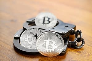 Silver Bitcoin coins and handcuffs on wooden table. Law problems or arrest concept